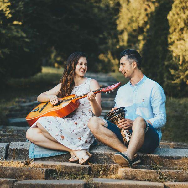 Moça toca violão e rapaz toca instrumento percussivo em um parque