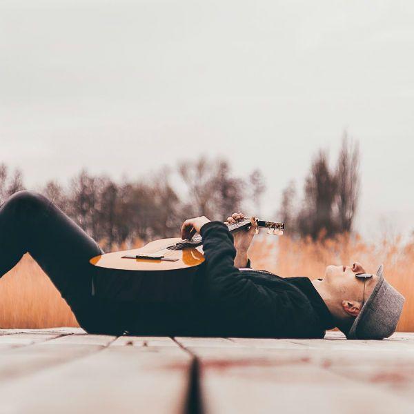 Homem deitado, relaxando, e dedilhando um violão