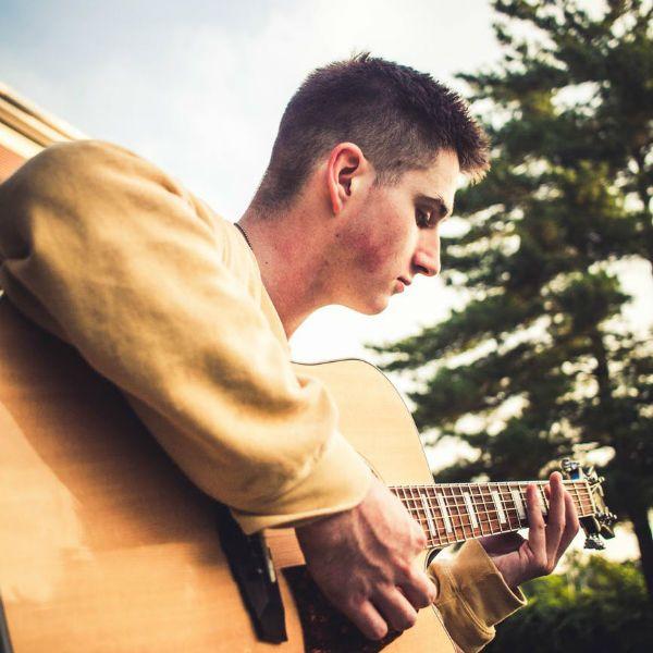Rapaz toca violão de aço, com uma paisagem natural ao fundo