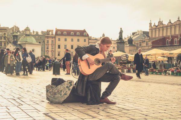 Músico toca violão no banco de uma praça