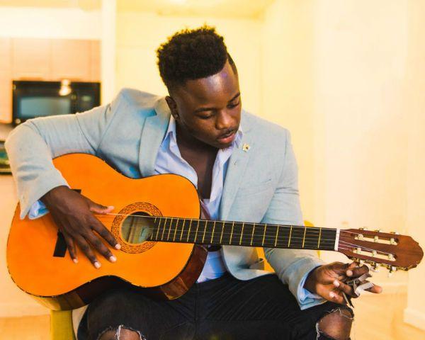 Músico negro afina as cordas de um violão de nylon