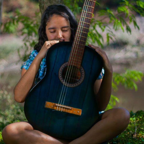 Menina de olhos fechados segura um violão