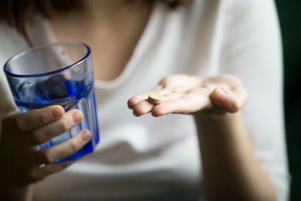 Mãos femininas segurando remédio e um como d'água