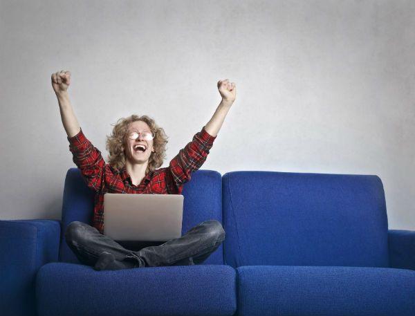 Jovem, nerd, sentado num sofá azul e rindo diante do notebook