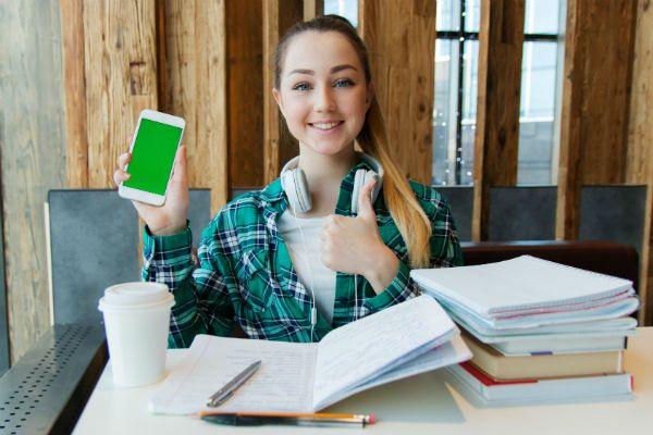 Menina jovem, estuda em casa e ouve música