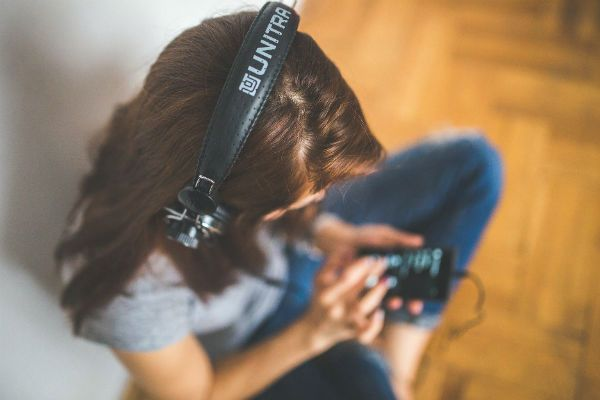 Garota jovem ouve música, no fone de ouvido, sentada no chão de sua casa