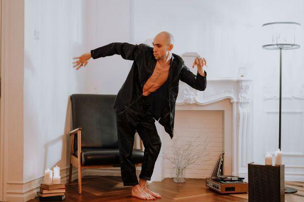 Homem descalço, em casa, dançando e ouvindo disco de vinil