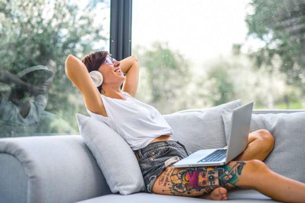 Mulher sorridente faz home office, no sofá de casa, e ouve música