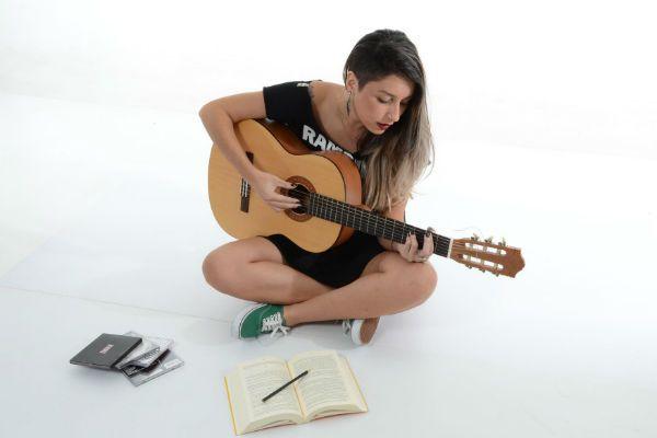 Menina toca violão com coluna curvada