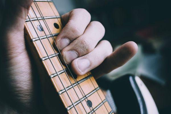 Os dedos que formam os acordes em um instrumento musical