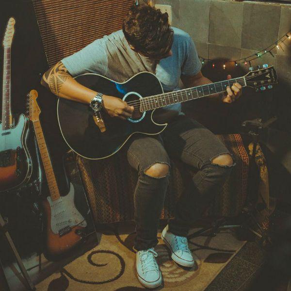 Joven aplicando los tips para tocar la guitarra
