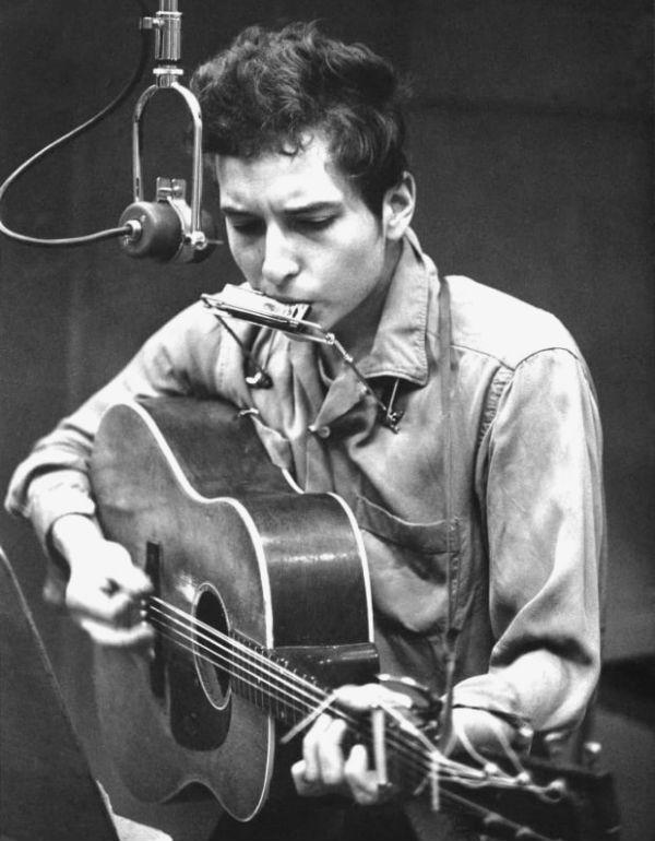 Bob Dylan toca violão e gaita ao mesmo tempo