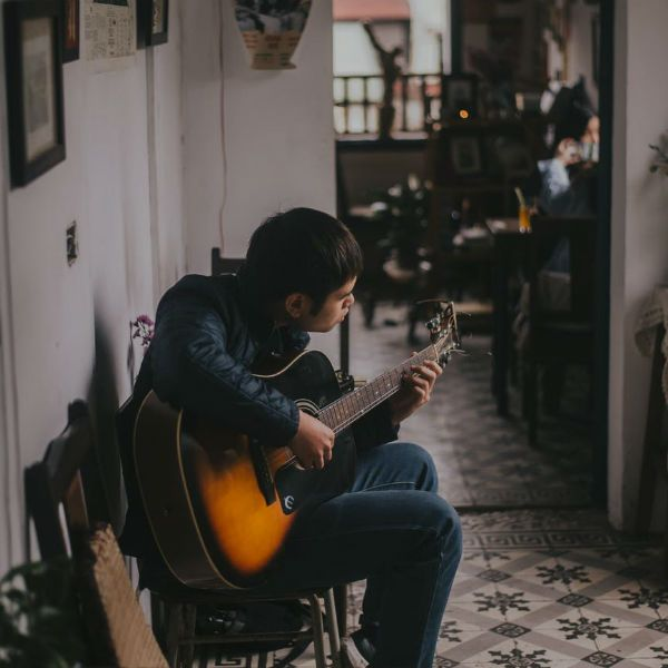 Niño estudiando los fundamentos de la guitarra acústica