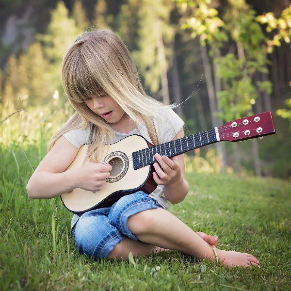 Sentada na grama, jovem menina loira toca violão com cordas de aço