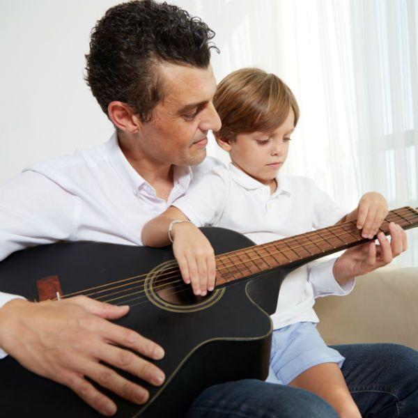 Pai e filho se divertem com violão