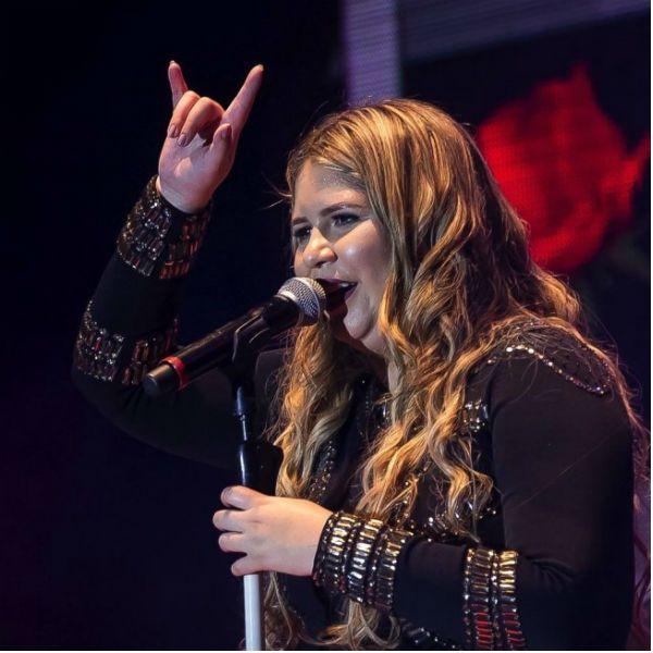 Cantora Marília Mendonça faz sinal de chifre com os dedos
