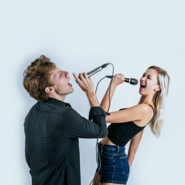 Dos cantantes con micrófonos haciendo un dúo