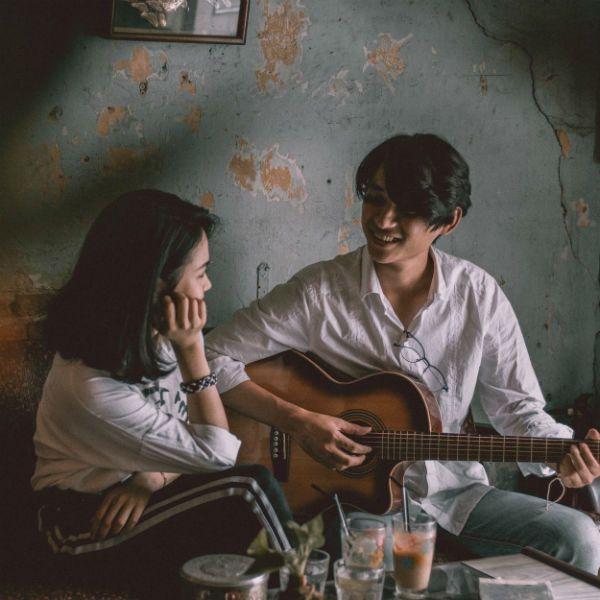 Casal, sentado no sofá, ele toca violão e ela admira