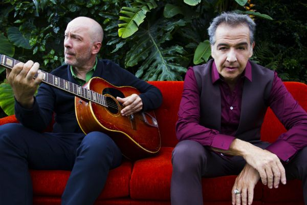Edgar Scandurra tocando o violão e Nasi, ambos do IRA!, sentados num sofá vermelho