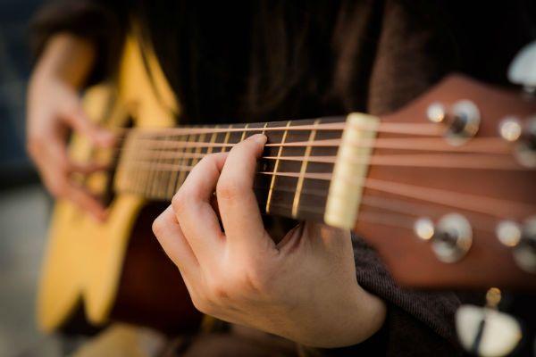 Mulher toca violão de seis cordas de aço