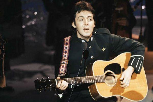 Paul McCartney ainda jovem e tocando seu violão de aço, de forma invertida