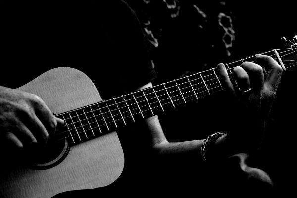 Músico faz acorde complexo no violão de seis cordas de aço