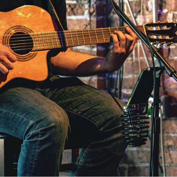 Músico toca violão e observa cifras simplificadas de músicas no smartphone