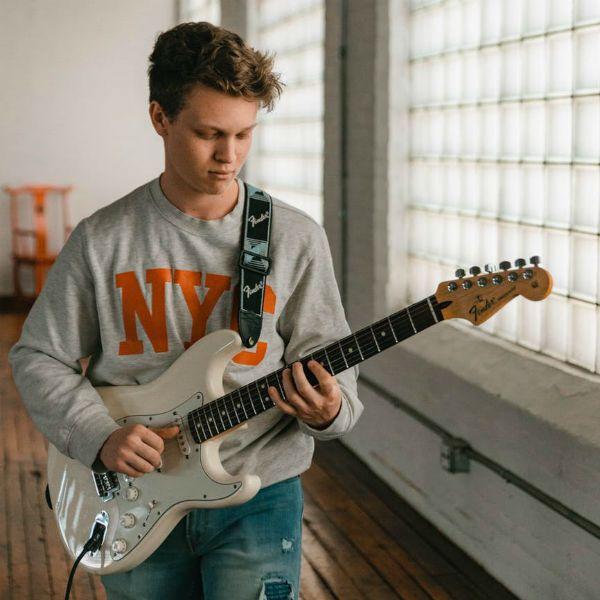 Estudante de guitarra treina exercício de digitação em sua Fender Stratocaster
