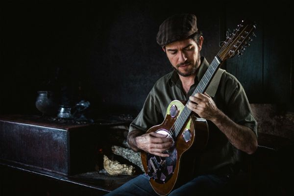 Zé Helder sentado no fogão à lenha e segurando tocando viola