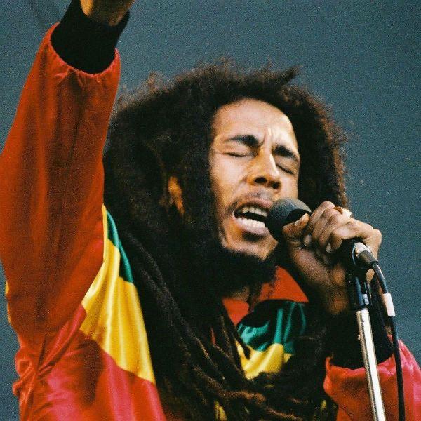 Bob Marley cantando ao vivo, com sua jaqueta estilizada nas cores do reggae