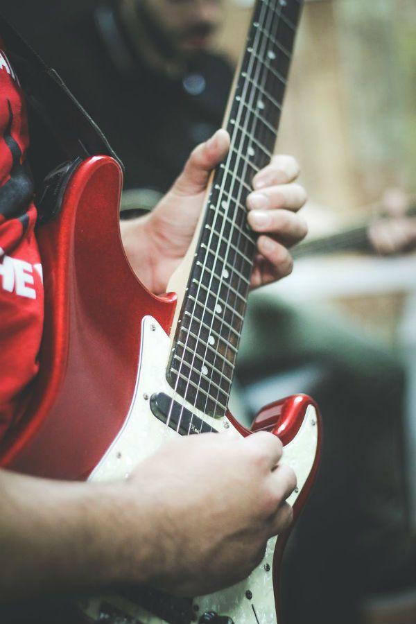 Guitarrista faz um lick em sua guitarra stratocaster vermelha