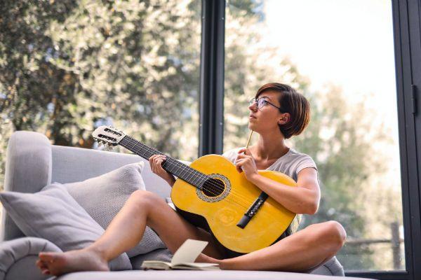 Mulher toca violão sentada no sofá