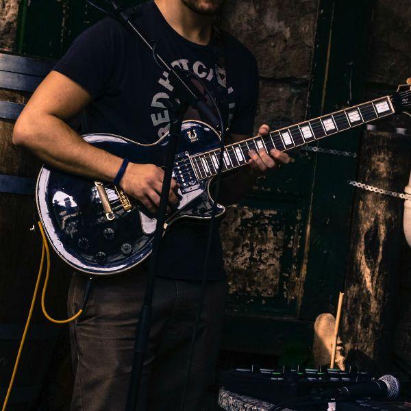 Rapaz faz um solo de guitarra em les paul