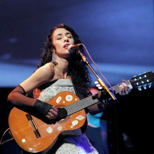 Marisa Monte tocando violão, de olhos fechados, durante uma apresentação