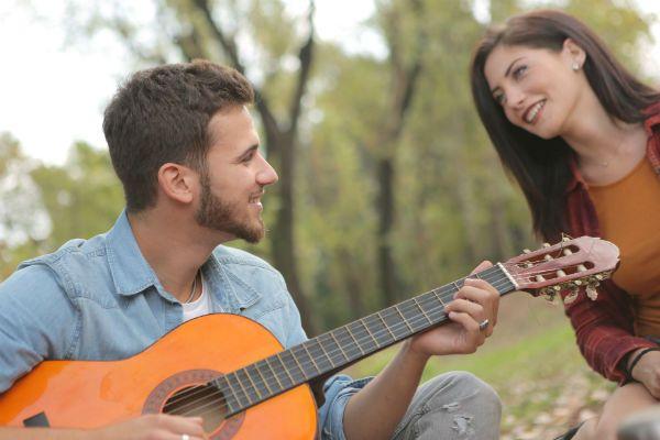Casal de namorados aproveitam um dia no parque, ele toca violão pra ela