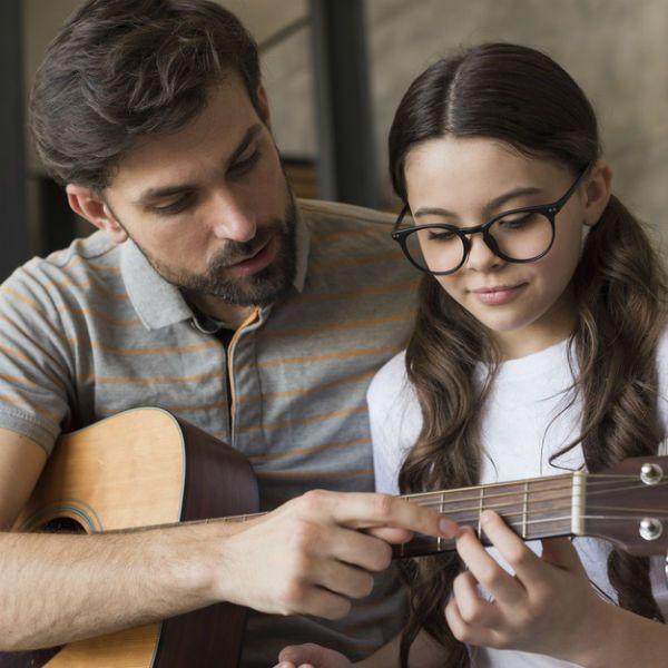 menina e pai tocam violão juntos