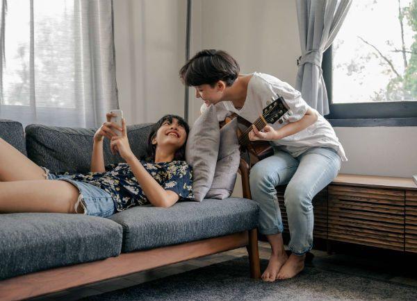 Garota tocando violão, enquanto sua aniga está deitada no sofá e com celular em mãos