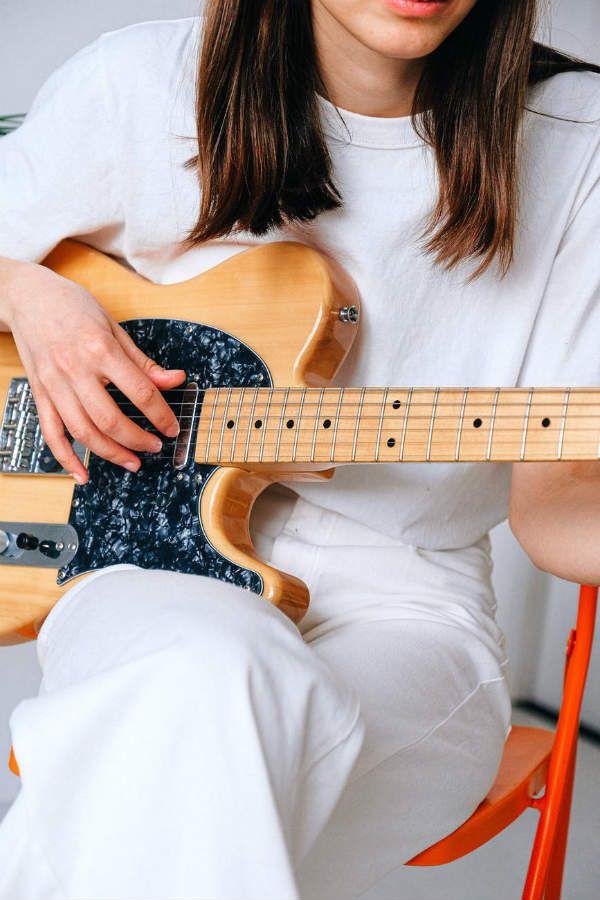 Guitarrista mulher segura toca com uma fender modelo telecaster