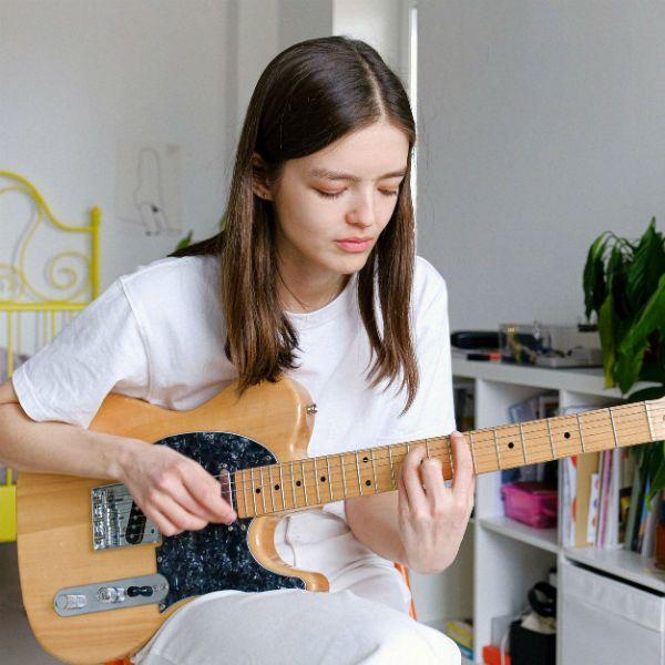 Garota estudante de guitarra toca um acorde com pestana em sua telecaster