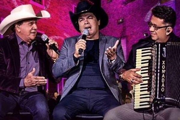 Sentados, os membros do Trio Para Dura gravaram músicas do DVD Pensa Num Trem Que Dói