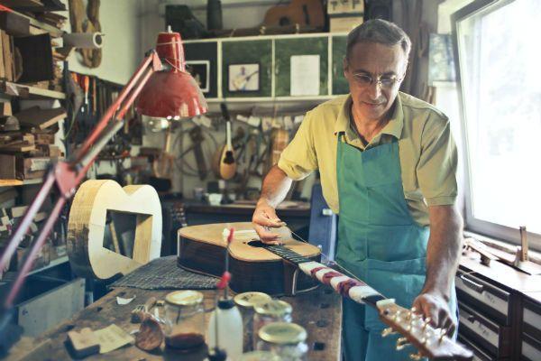 Luthier regulando corda de violão