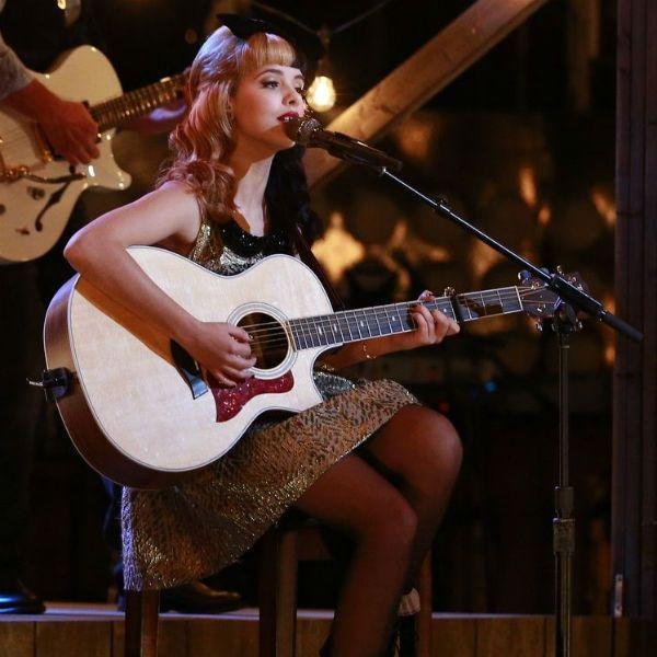 Melanie Martinez toca violão, durante sua passagem pelo The Voice