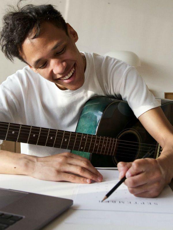Com violão no colo, jovem músico anota cifras de música que pretende enviar para o CIfra Club