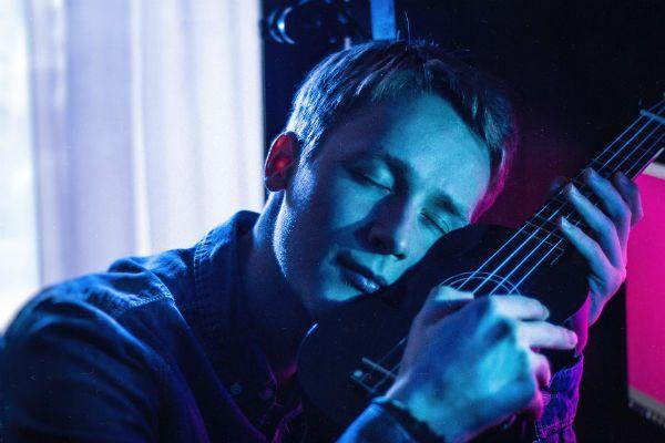 Rapaz jovem e de olhos fechados segura ukulele