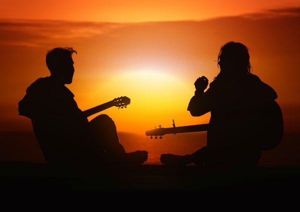 Dupla toca violão e observa o pôr do sol