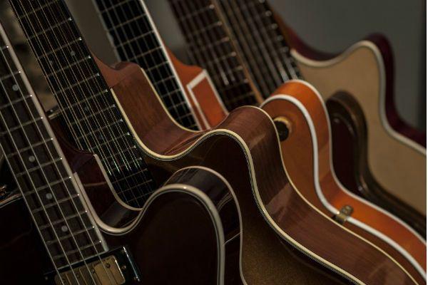 Guitarras e violões perfilados em uma estante de loja especializada