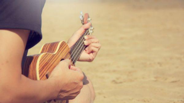 Músico toca ukulele na praia