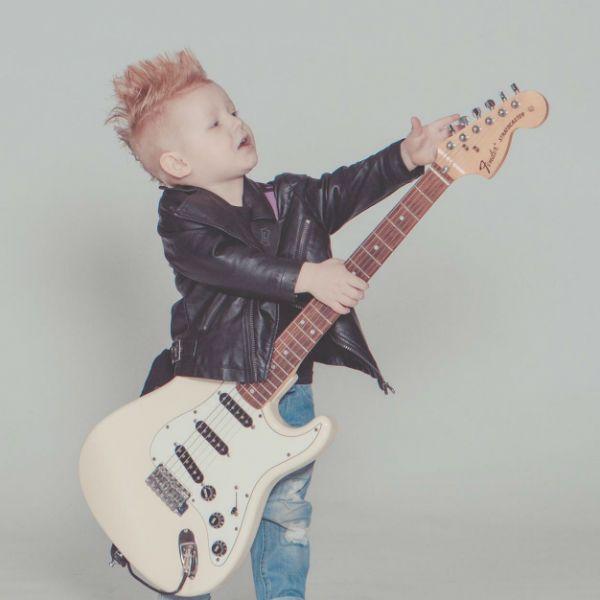 Menino vestido de roqueiro e tocando guitarra