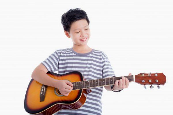 Menino asiático tocando violão