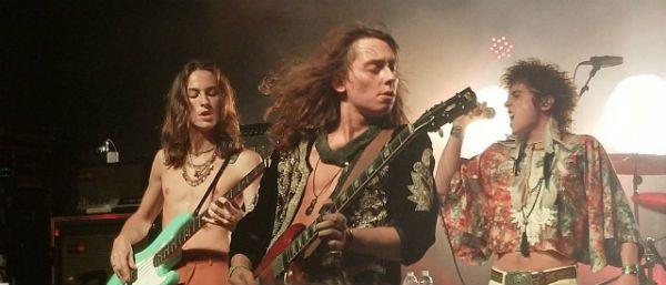Em meio aos seus irmãos, Jake Kiszka faz um solo de guitarra